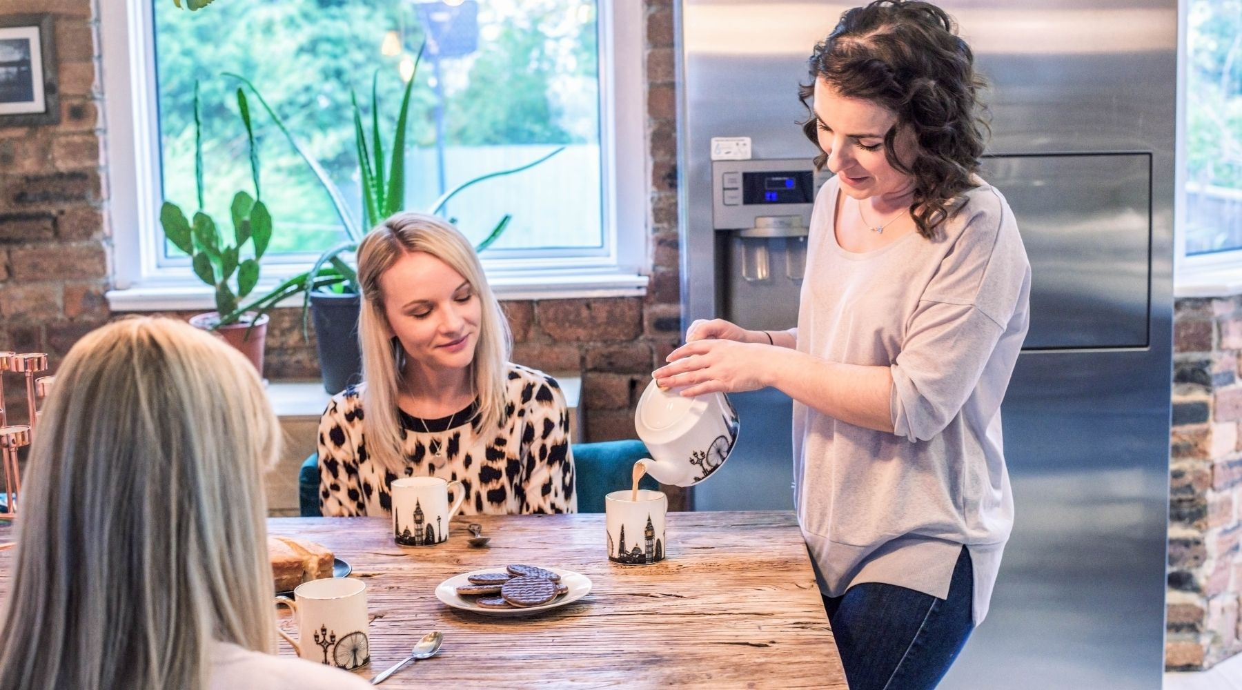 Brown haired lady pours tea from a london landmark teapot into a london landmark mug. Two of her friends are sat at the table. There is a plate of chocolate biscuits on the table.