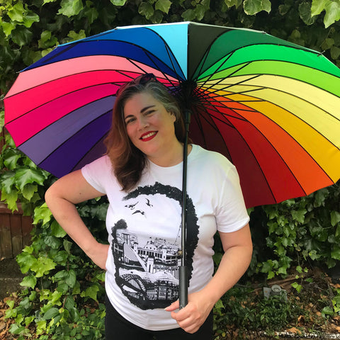 Photograph of designer Corinne Lewis-Ward wearing a black and white tshirt while holding a rainbow umbrella