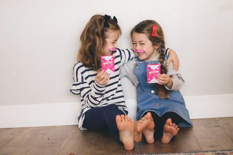 Two girls holding up Valentine's Day candy