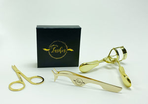 Black and gold lash box, with gold scissors, tweezers and lash curler.