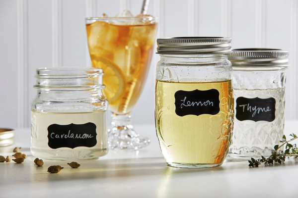Photo of three mason jars filled with simple syrups and one glass of iced tea.