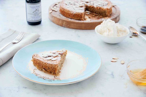 Photo of slice of Almond Torte Dessert with bottle of Vanilla Extract and fresh whipped cream on marble table