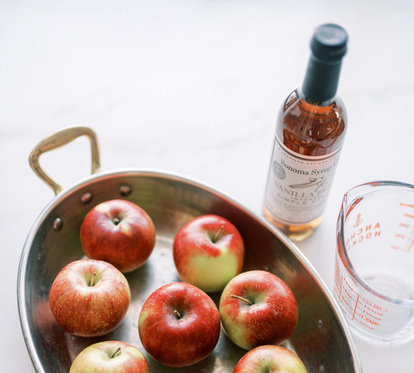 Photo of a large dish full of fresh red apples next to a measuring cup and bottle of Vanilla Bean Simple Syrup.