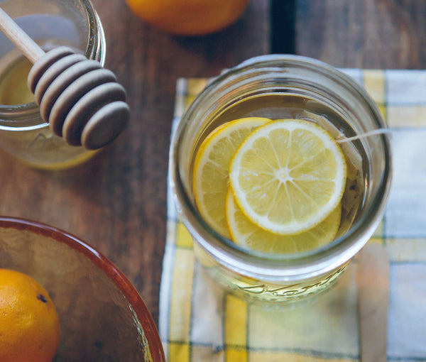 Photo of a mason jar with lemon slices and tea bag, sitting next to a honey comb spoon for a warm Lemon Hot Toddy.