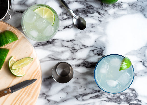 Picture of 2 glasses full of classic lime gimlet cocktail on marble table