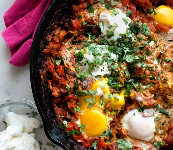 Photo of a cast iron pan filled with a delicious shakshuka with runny egg yolks and cilantro on top.