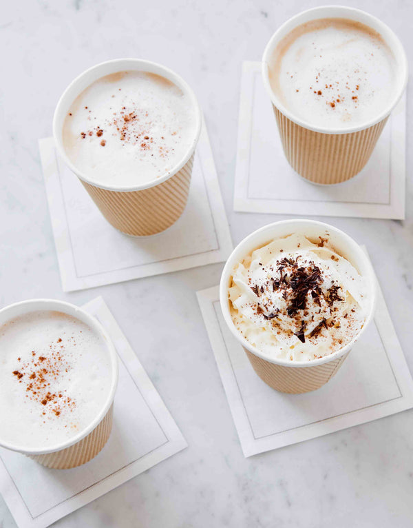 Photo of four coffees, lattes, and cappuccino drinks in kraft cups. Topped with whipped cream, cocoa powder, and cinnamon.