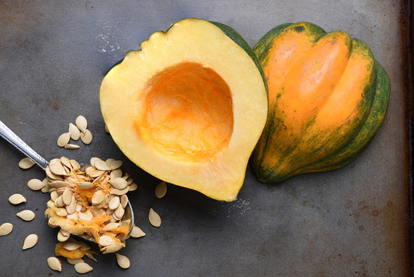 Photo of a baked squash with seeds removed on a dark surface. The first step of this recipe before it is baked.