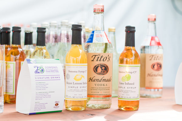 Photo of a festival booth with a variety of Sonoma Syrup's and a large bottle of Tito's Vodka for the Sonoma International Film Festival.