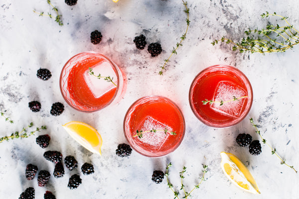Picture of 3 glasses with ice, pink lemonade, and mint spring surrounded by lemon slices and black berries
