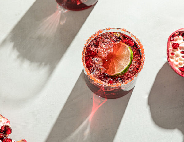 Picture of two deep red margaritas in cocktail glasses topped with a fresh lime and salt rim