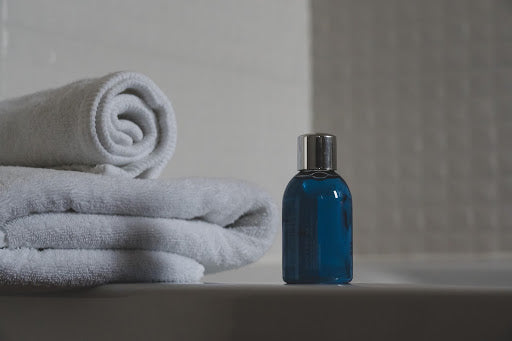 A blue bottle of shampoo and white towels