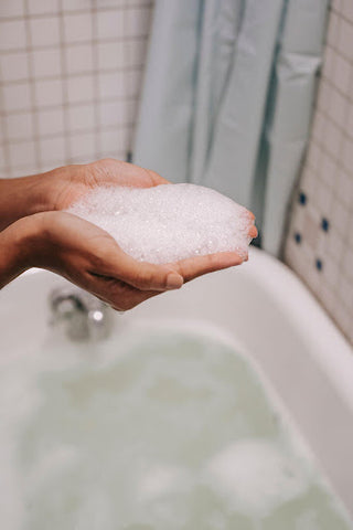 Person with handful of soap suds