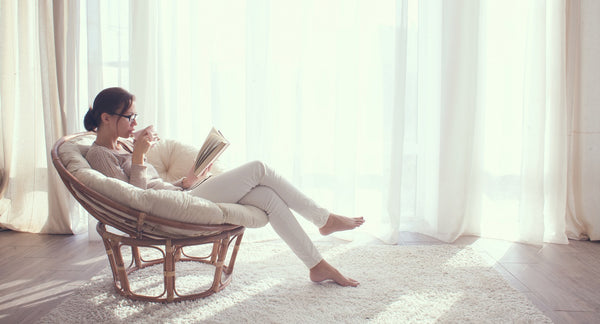 Young woman at home sitting on modern chair in front of window relaxing in her living room and reading a book