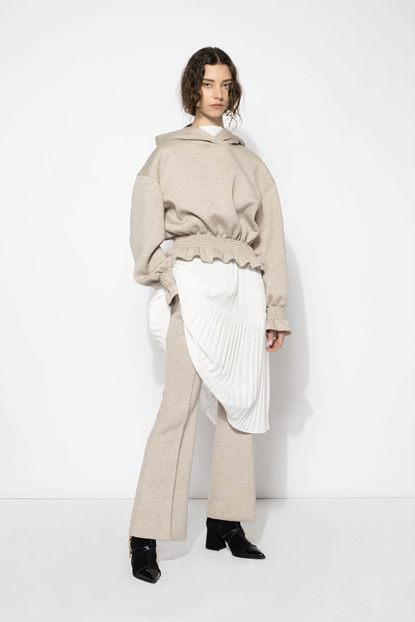 Photograph of model wearing Adeam's fashion look of a plain white dress, layered underneath a light beige ruffled hoodie and light beige sweatpants.