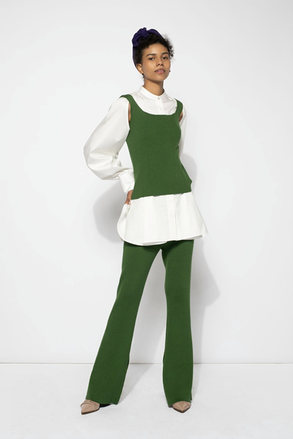 Adeam's fashion piece of a model wearing a white, oversized shirt underneath a vibrant green sweater vest, coupled with green pants and beige shoes