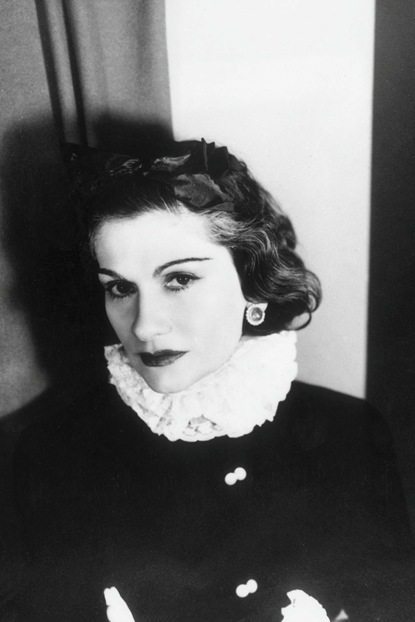 Black and white photograph of designer Coco Chanel wearing a black dress with a white ruffled neck