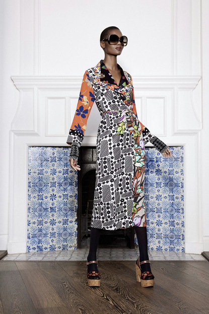 Photograph of a model wearing Duro Olowu's floral pattern dress with black flowers on a white background mixed with yellow and blue larger flowers on a orange background. The model is accessorising this dress with a pair of large black circular sunglasses, black tights and cream shoes.
