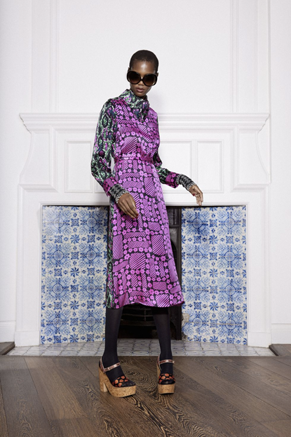 Image of a model wearing Duro Olowu's dress with purple floral patterns on a black background. The model is coupling this look with large, black circular sunglasses, black tights and beige platform shoes.
