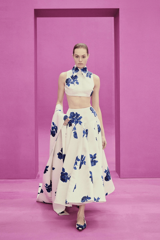 Image of model wearing Emily Wickstead's dress on a pink runway. The white dress is middle-less and sleeveless and has a blue floral pattern. It is couples with black high heels.