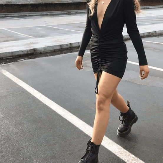 Image of influencer on high street wearing our Ukiyo fitted satin black dress with matching black boots