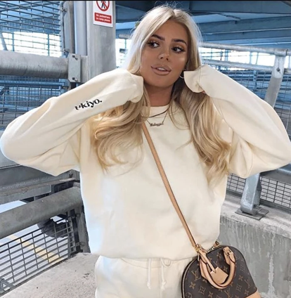 Influencer wearing our Ultimate Ukiyo cream tracksuit jogger set, coupled with a black and cream fabric handbag