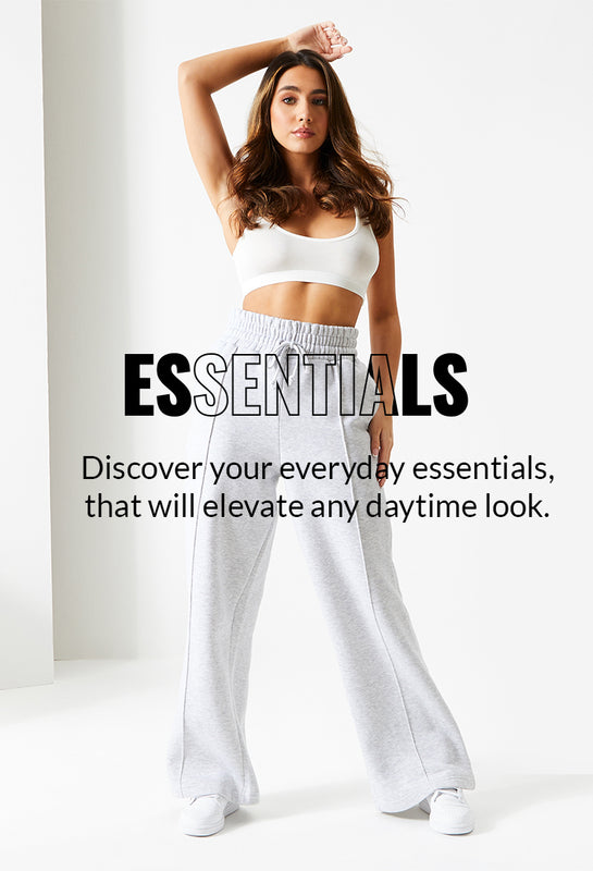 "Image of a model wearing our Ice Grey Wide Leg Joggers and a white crop top behind the text ""Essentials. Discover your everyday essentials, that will elevate any daytime look"""