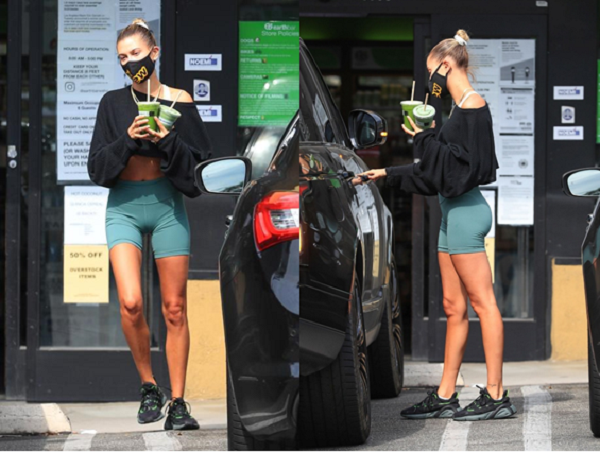 Model Hailey Bieber wearing  teal high waisted cycling shorts and relaxed cropped sweater matched with some chunky, sporty trainers