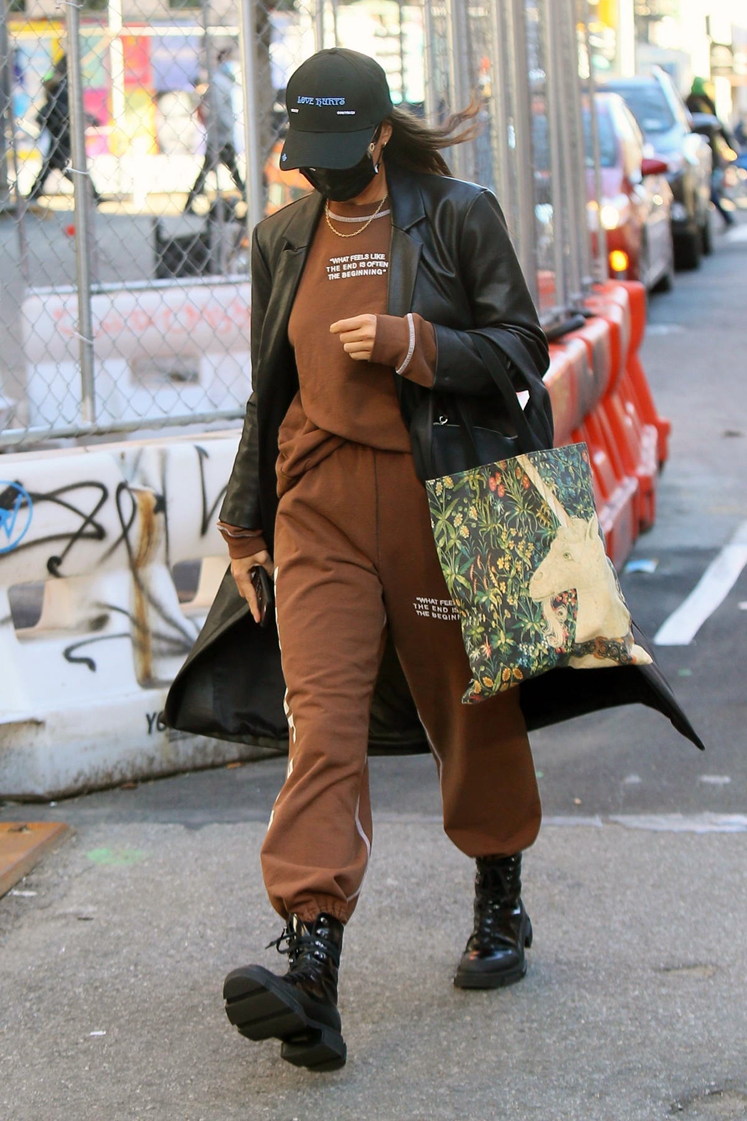 Photograph of Irina Shayk wearing a cocoa coloured sweatsuit combo layered with a Matric leather trench and black combat boots
