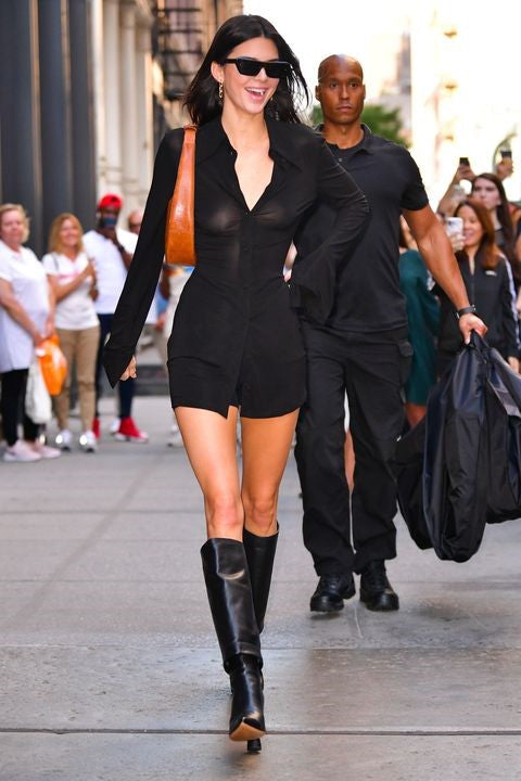 Photograph of Kendall Jenner wearing a short button-up black dress, coupled with tall black boots