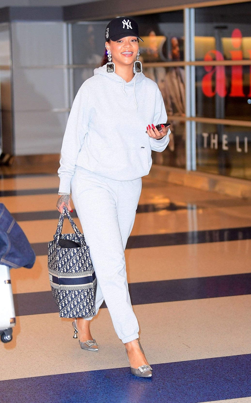 Photograph of Rihanna wearing extreme pendant earrings, silver high heels and a white tracksuit