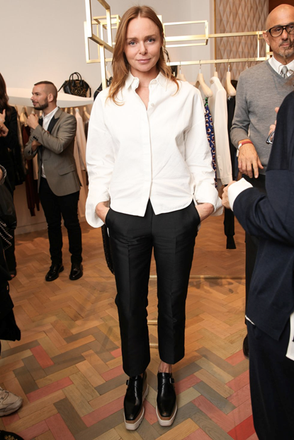 Photograph of designer Stella McCartney in a white button up shirt and black suit trousers