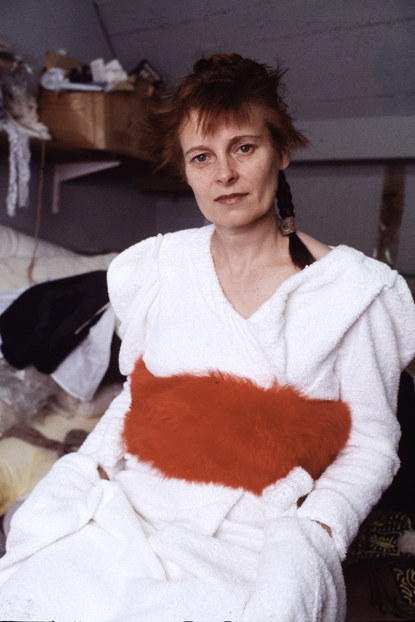 Photograph of designer Vivienne Westwood in a white robe with a fluffy red mid section