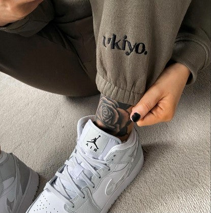 Photograph of influencer tying her white Air trainers whilst showing off the cuff of her Ukiyo Frosted Olive Jogger