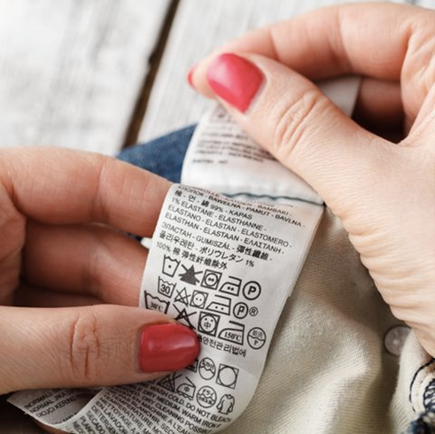 Photograph of woman reading the washing machine tag on an item of clothing