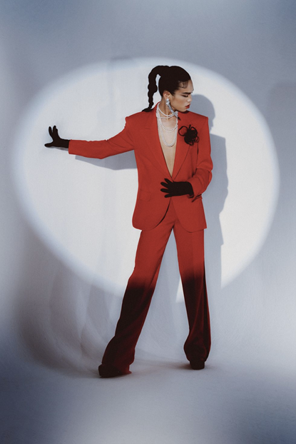 Prabal Gurung's concept look of a red suit jacket with red suit pants, black gloves and a black fabric broach.