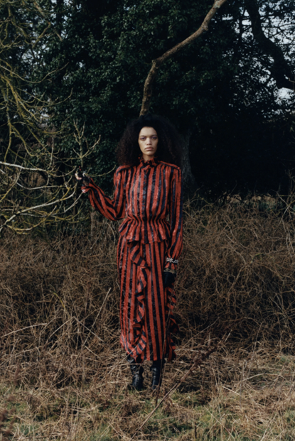 Image of model in woodland area wearing Preen by Thornton Bregazzi's red and black pinstripe jumpsuit, paired with tall black boots and black gloves