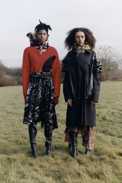 Photograph of two models next to each other wearing Preen by Thornton Bregazzi pieces. The model on the left is wearing a floral dress layered with a red cardigan over the top, a black beret and floral scarf. The model on the right is wearing another floral dress that is almost entirely covered by a long, leather overcoat. This look is coupled with tall black boots and a floral scarf that matches the dress.