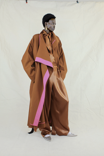 Image of model wearing Roksanda's dark orange/light brown flowy jumpsuit and robe, with a pink trim on the robe. This is coupled with gold earrings and white shoes.