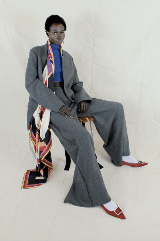 Image of model wearing Roksanda's blue turtleneck jumper underneath an oversized fabric grey suit. This is accessorised with an abstract, multi-coloured scarf and brown shoes.