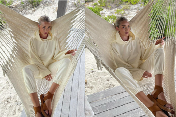 Rosie Huntington Whitely wearing a matching vanilla sweatshirt and jogging bottoms paired with some cross over tan sandals in a cream hammock