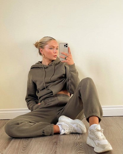Selfie of influencer wearing our Ukiyo Frosted Olive Jogger Set paired with white trainers and hoop earings