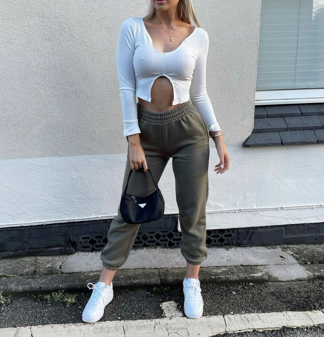 Shoulder-down photograph of influencer wearing our Ukiyo Frosted Olive Joggers and Off White Split Front Long Sleeve Crop Top paired with white trainers and a small black clutch bag