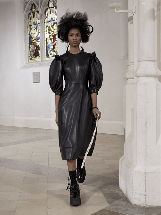 Photograph of a model wearing Simone Rocha's long, black leather dress coupled with high laced black boots. The model is also clutching a string of pearls.