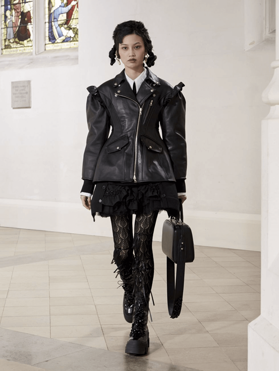 Photograph of Simone Rocha's outfit piece of a black ruffled shirt and white shirt with a black tie, underneath an oversized black leather jacket. The look is coupled with black patterned tights, high laced black boots and a black handbag