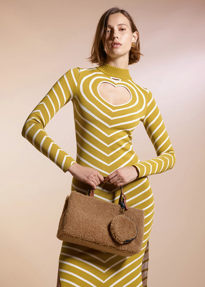 Photograph of Staud's fashion look of a yellow and white striped dress with a heart shape cut out of the chest area. The model is also carrying a dark beige handbag.