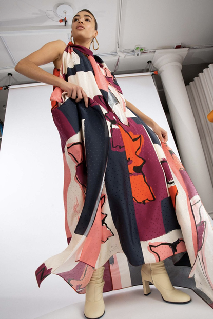 Photograph of a model wearing Tanya Taylor's light, flowy dress with orange, red and white shape-based print