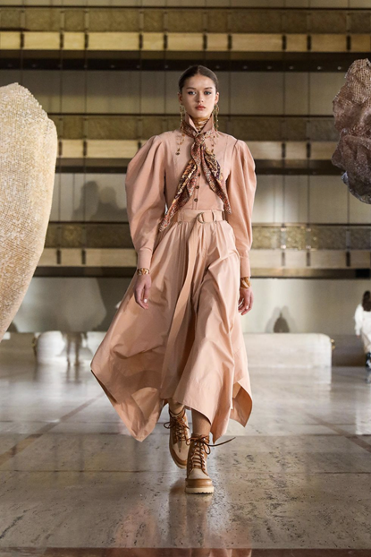 Ulla Johnson's peach pink dress with oversized sleeves and buttons, coupled with a brown pattern scarf and brown boots