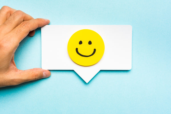 Yellow smiley face on a message icon shaped piece of paper on a light blue background