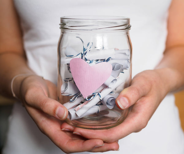 Person holding transparent jar with a pink heart on the front and white paper scrolls tied with with blue and white thread inside